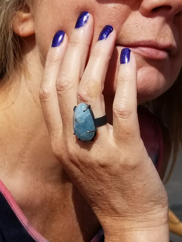 Woman wearing large blue ring