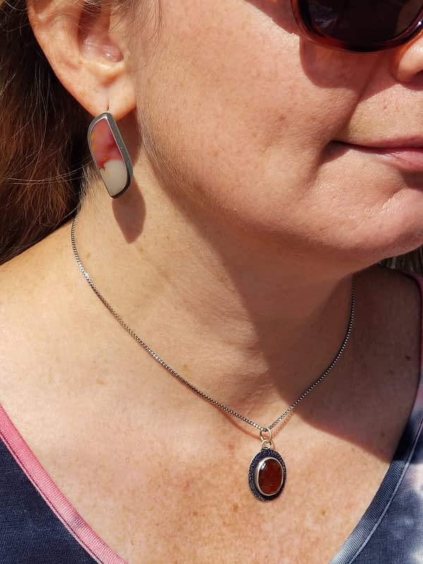 Woman wearing orange necklace and earrings